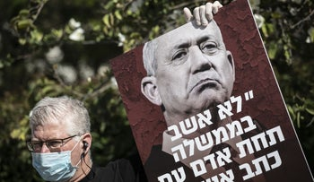 A protester outside Benny Gantz's home in Rosh Ha'ayin, March 28, 2020. The sign features Gantz's quote that he would not serve in a government alongside an indicted prime minister.