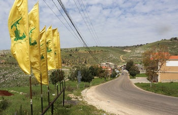 Hezbollah flags flutter along an empty street, amid the coronavirus outbreak, at the entrance of Mays Al-Jabal village, close to the Lebanese border with Israel, March 26, 2020.