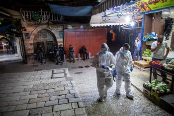 Magen David Adom workers are seen walking through the Muslin Quarter of Jerusalem's Old City, April 2020.