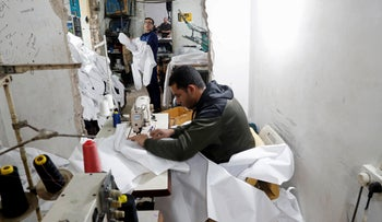 Palestinians make protective overalls meant to shield people from the coronavirus, to be exported to Israel, at a local factory, in Gaza City, March 30, 2020.