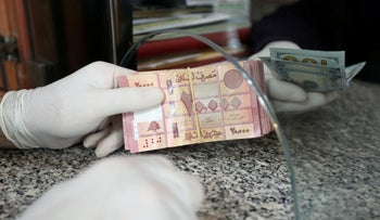 A customer wearing gloves holds Lebanese pounds at a currency exchange store, during a countrywide lockdown to combat the coronavirus in Beirut, Lebanon April 3, 2020