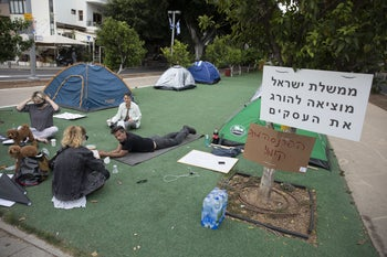 Protesters at Tel Aviv's Rothschild Boulevard, the sign says the government is killing business.