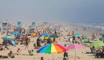 People enjoy the beach amid the novel coronavirus pandemic in Huntington Beach, California on April 25, 2020