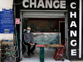 A man sits inside his money exchange shop in Jerusalem on April 21, 2020.