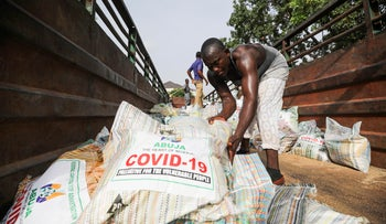 Men load sacks of rice among other food aid in a truck in Abuja, Nigeria April 17, 2020.