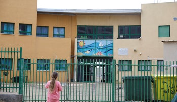 A girl looks at a school closed because of the coronavirus, Hadera, March 13, 2020