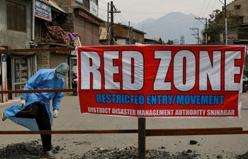 """A Kashmiri man crosses a barricade in an area declared as a """"red zone"""" because of coronavirus infections during lockdown in Srinagar, Indian-controlled Kashmir. April 14, 2020"""