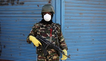 An Indian paramilitary soldier stands guard wearing protective gear against coronavirus in a residential area of Srinagar, Indian-controlled Kashmir. April 11, 2020