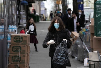 A woman wearing a mask and gloves leaves Kahan's Superette, a kosher grocery store, in Brooklyn's Crown Heights neighborhood. April 7, 2020
