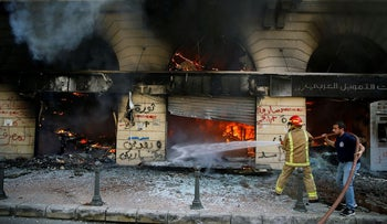 Firefighters extinguish a fire at a branch of the Credit Libanais Bank that was burnt by anti-government protesters, in the northern city of Tripoli, Lebanon, Tuesday, April 28, 2020