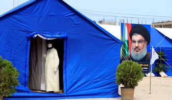 A medic wearing protective gear stands inside a tent facility set up by Hezbollah to test for coronavirus in al-Ghaziyeh, southern Lebanon March 31, 2020.