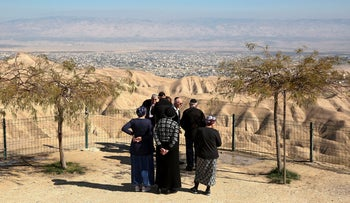 Jewish settlers stand at a viewpoint overlooking the West Bank city of Jericho from the Jewish settlement of Mitzpeh Yeriho, January 26, 2020.