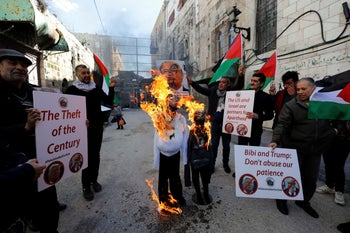 Palestinian demonstrators burn effigies depicting U.S. President Donald Trump and Israeli Prime Minister Benjamin Netanyahu during a protest in Hebron, West Bank, February 28, 2020.