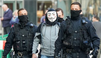 A man is escorted by police officers for identification by authorities in Chemnitz, Germany, April 24, 2020.