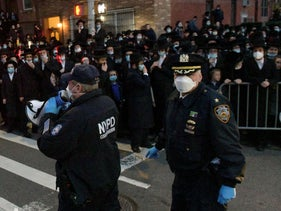 Police instruct a crowd as hundreds of mourners gather in Brooklyn, April 28, 2020