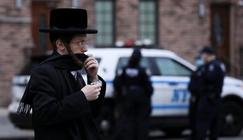 A man moves his scarf to cover his face as he passes NYPD officials stationed in Williamsburg, NYC, April 30, 2020.