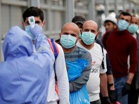 A healthcare worker checks the body temperature of Palestinian workers returning from Israel, amid concerns over the spread of the coronavirus, outside the Israeli-controlled Meitar checkpoint.