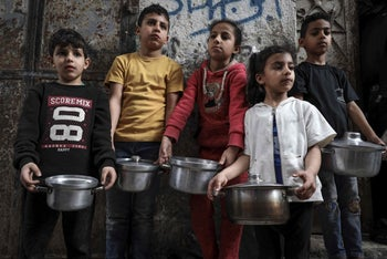 Palestinian youth queue to receive a portion of soup during the Islamic holy month of Ramadan in Gaza City on April 24, 2020, during the the COVID-19 coronavirus pandemic.