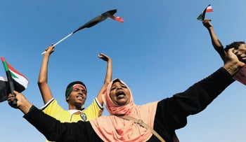 A Sudanese woman chants slogans and waves a national flag to celebrate a power-sharing agreement during a transition period leading to elections, Khartoum, Sudan, July 5, 2019.
