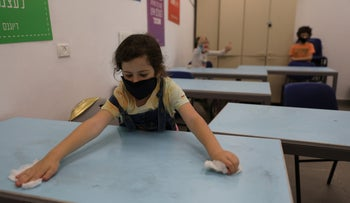 An Israeli child disinfects her desk at a school in Jerusalem, May 3, 2020