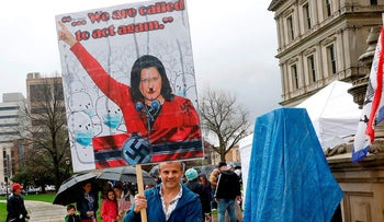 A protestor with a sign that has Michigan Gov. Gretchen Whittmer depicted as Adolph Hitler is seen at an American Patriot Rally organized by Michigan United for Liberty protest for the reopening of businesses, on the steps of the Michigan State Capitol in Lansing, Michigan on April 30, 2020
