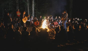 Song leaders join campers and counselors in celebrating the end of Shabbat Havdalah service around the campfire at URJ Camp Harlam, in Kunkeltown, Penn.