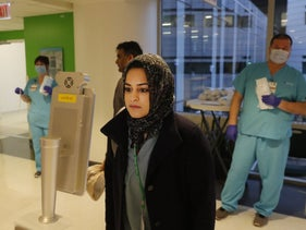 Respiratory therapist Jumana Azam pauses before a face temperature scanner as she reports for her early morning shift at RUSH Hospital in Chicago.