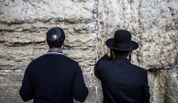 A member of an LGBT delegation and an ultra-Orthodox man praying at the Western Wall in Jerusalem's Old City in 2017.