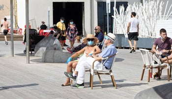 People sit outside at Tel Aviv Port as coronavirus restrictions begin to be eased, May 2, 2020