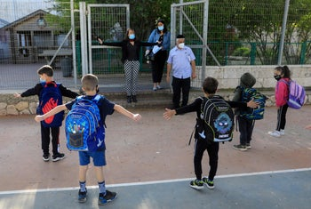 Pupils are shown how to maintain social distancing, upon return to school after the COVID-19 lockdown, at Hashalom elementary in Mevaseret Zion, in the suburbs of Jerusalem, May 3, 2020.
