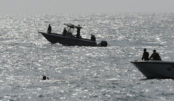 Security forces investigate near the shore in the port city of La Guaira, Venezuela, Sunday, May 3, 2020.
