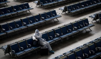 A passenger wears a hazmat suit as a precaution against the COVID-19 coronavirus as he waits for a train at Hankou Railway Station in Wuhan, China, May 2, 2020.