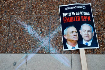 A placard with a picture of Prime Minister Benjamin Netanyahu (R) and his rival-turned-partner Benny Gantz, lies on the street during a demonstration in Tel Aviv's Rabin Square, May 2, 2020.