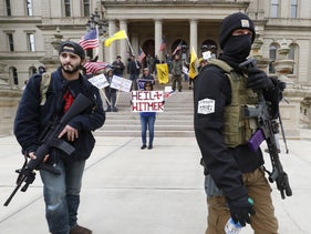 """Protesters carrying rifles near the steps of the Michigan State Capitol building in Lansing, April 15, 2020. Another protester holds a sign stating:""""Heil Witmer."""""""