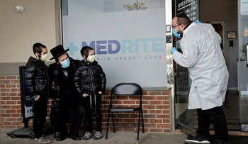 An Orthodox Jewish man and two children wear protective face masks as they speak to a healthcare worker in the New York City suburb of Spring Valley, April 23, 2020.