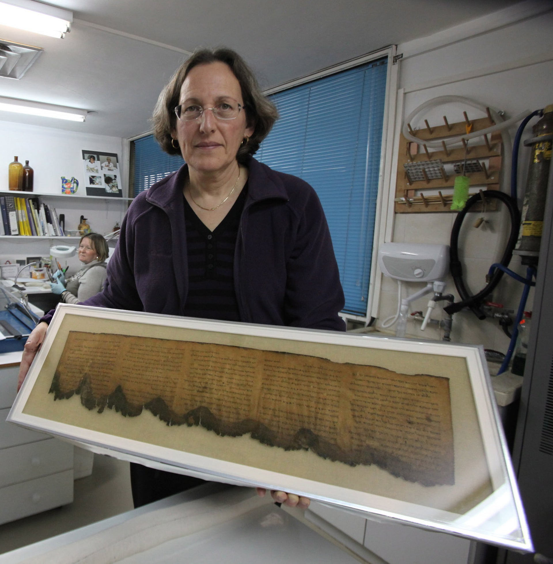 Pnina Shor with a relatively legible piece of the Dead Sea Scrolls