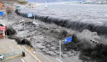 a tsunami floods over the breakwater protecting the coastal city of Miyako at Heigawa estuary area after northeastern Japan was hit by a powerful earthquake.