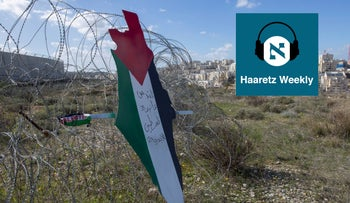 A placard with the colors of the Palestinian flag on a barbed-wire fence surrounding the Israeli separation wall and the settlement of Mod'in Ilit, near Ramallah, in Jan. 2020.