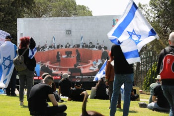 Protesters watch the Supreme Court hearings on Prime Minister Benjamin Netanyahu and Benny Gantz's coalition deal from a Jerusalem park, May 3, 2020.