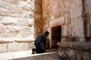 """An Orthodox Christian priest prays by the Church of the Nativity in the West Bank city of Bethlehem on April 18, 2020, before the arrival of the """"Holy Fire"""" from Jerusalem's Church of the Holy Sepulchre"""