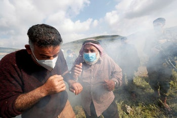 Palestinian demonstrators react to tear gas fired by Israeli troops during a protest against Israeli settlements near Nablus in the Israeli-occupied West Bank May 2, 2020