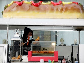 A vendor wears a protective face mask at a hotdog stand in a fashion shopping center in Ashdod, May 5, 2020.