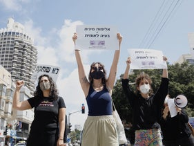 "A protest against violence against women, Tel Aviv, May 6, 2020. The large sign on the left says ""No silence."""
