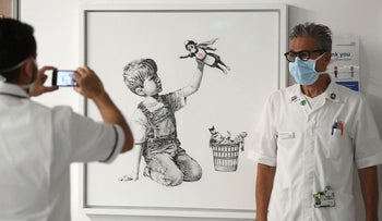 A member of staff has their photograph taken in front of the new artwork painted by Banksy during lockdown, entitled 'Game Changer', which has gone on display to staff and patients on Level C of Southampton General Hospital in Southampton, England, Thursday, May 7, 2020