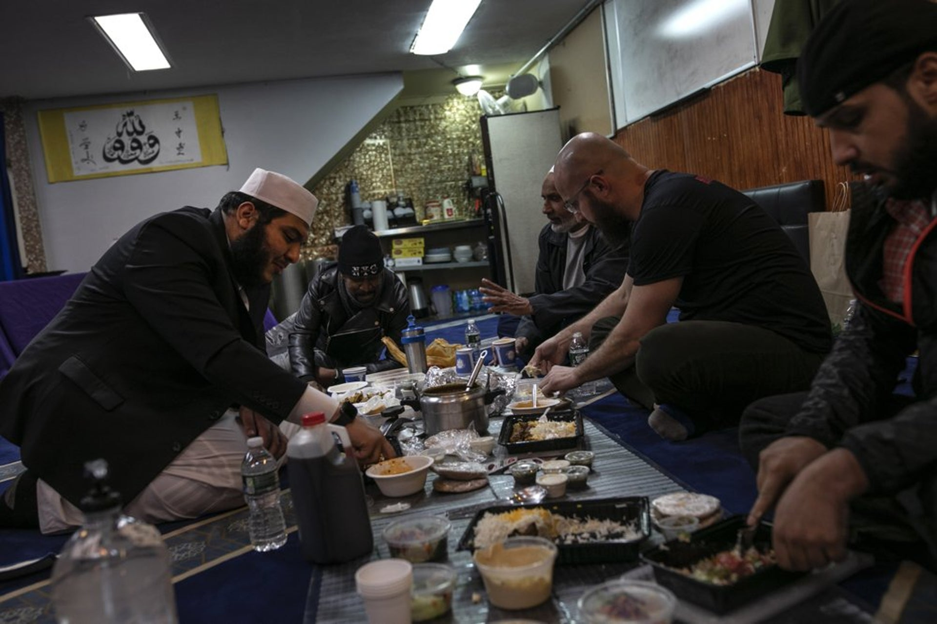 Ahmed Soliman, right, together with Mohamed Bahe, second right, end their day of fasting over a meal with Imam Abdullah Salem, left, between volunteering with Muslims Giving Back.