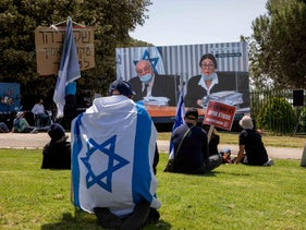 Israelis watch the High Court of Justice debate whether Benjamin Netanyahu can form a new government despite the criminal charges against him, Jerusalem's Rose Garden, May 3, 2020.