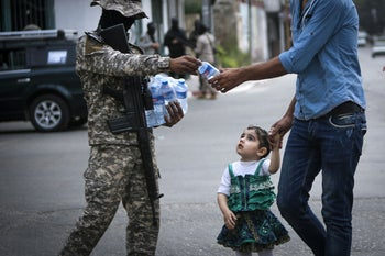 A member of the Palestinian Islamic Jihad hands out water bottles ahead of the breaking of the fast during the Islamic holy month of Ramadan in Gaza City, April 24, 2020.