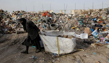 A woman collects recyclable garbage at dump, amidst concerns about the spread of the coronavirus disease (COVID-19), in Baghdad, Iraq, May 6, 2020.
