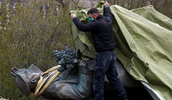 In this file photo taken on Friday, April 3, 2020, a worker covers the statue of a Soviet World War II commander Marshall Ivan Stepanovic Konev for removal from its site in Prague, Czech Republic