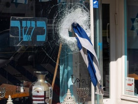 An Israeli flag sticks out of the window of HaCarmel kosher restaurant in Amsterdam, Netherlands, May 8, 2020, after a man smashed the window.